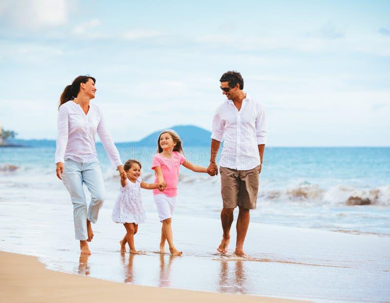 Lycklig ung familj som går på stranden royaltyfri bild