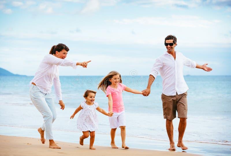 Lycklig ung familj som går på stranden royaltyfri fotografi