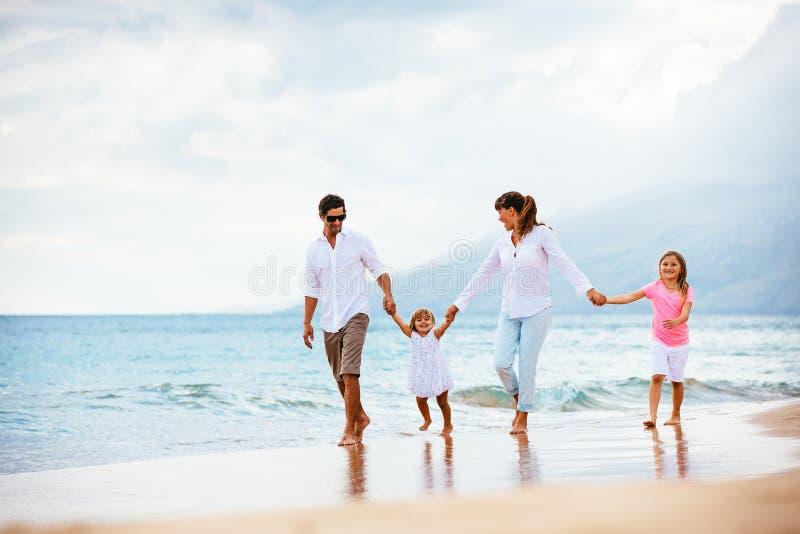Lycklig ung familj som går på stranden arkivbild