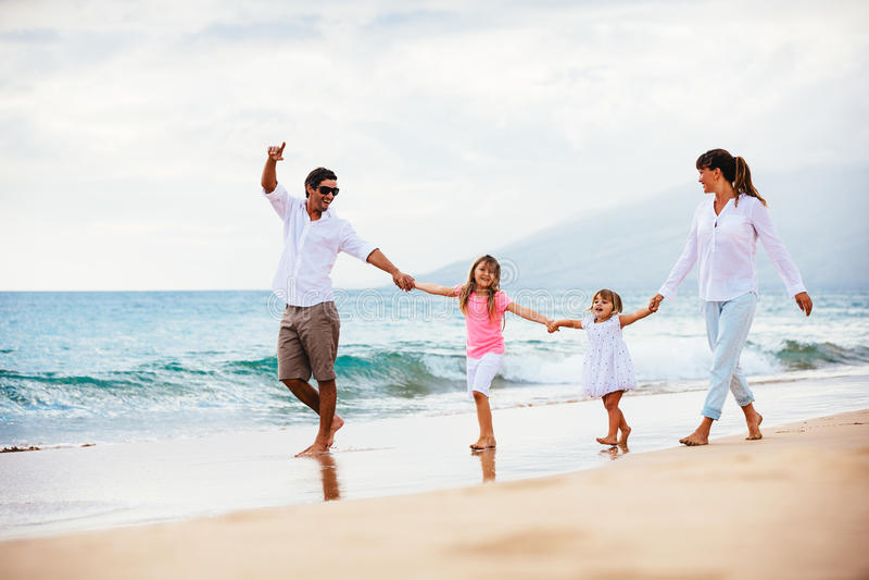 Lycklig ung familj som går på stranden arkivfoton