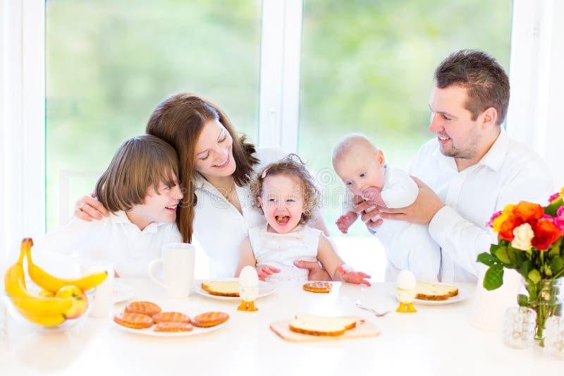 Lycklig ung familj som har frukosten på söndag royaltyfria bilder