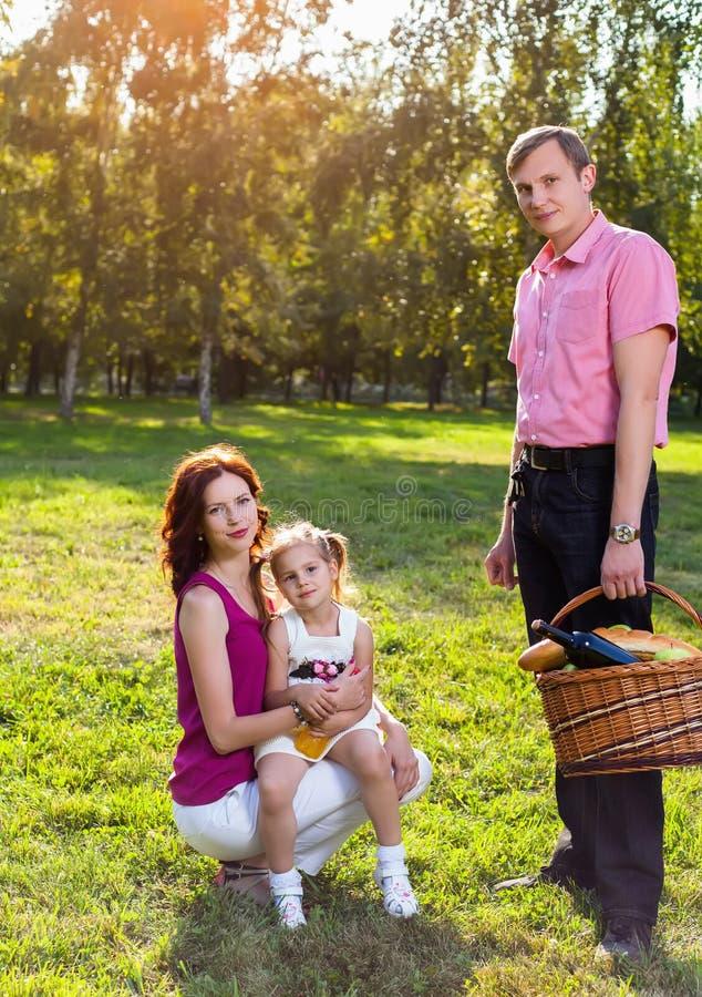 Lycklig ung familj som har picknicken på ängen royaltyfria foton
