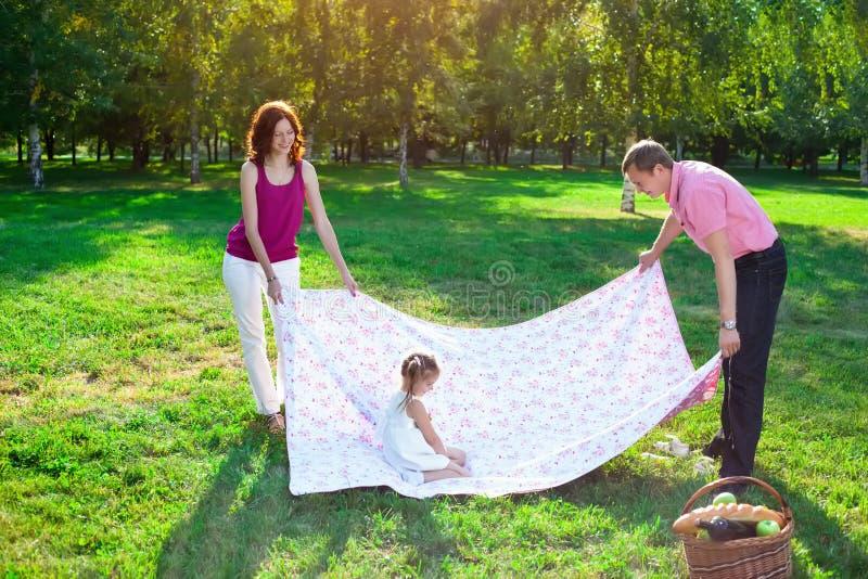 Lycklig ung familj som har picknicken på ängen royaltyfria bilder