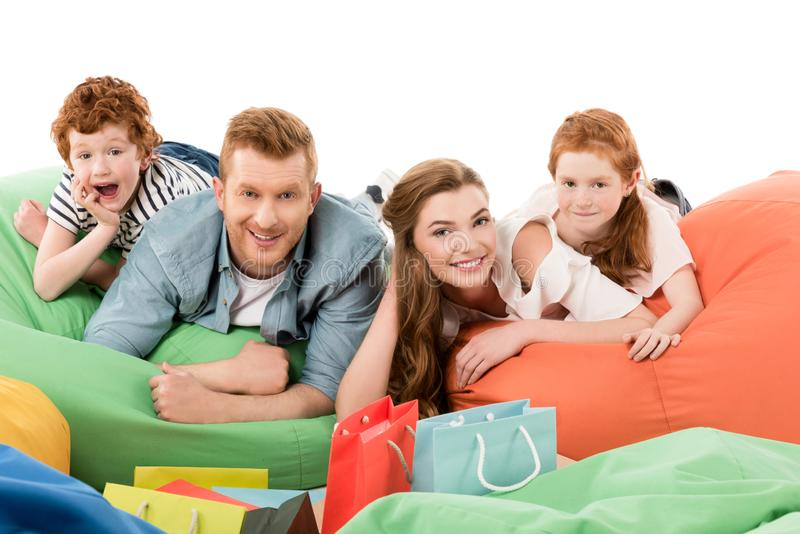 lycklig ung familj som ligger på stolar för bönapåse och after ler på kameran royaltyfri bild