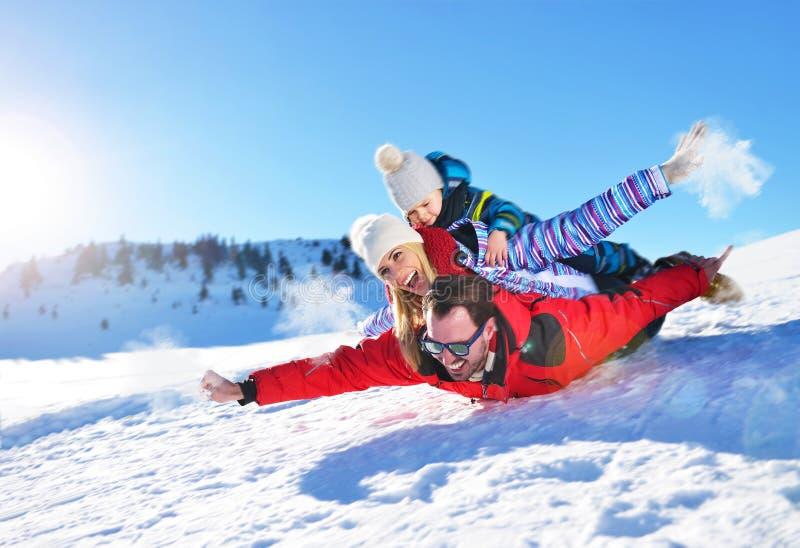Lycklig ung familj som spelar i ny snö på härliga soliga den utomhus- vinterdagen i natur arkivfoton