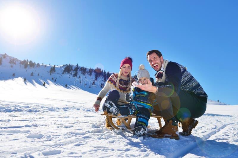 Lycklig ung familj som spelar i ny snö på härliga soliga den utomhus- vinterdagen i natur royaltyfri bild