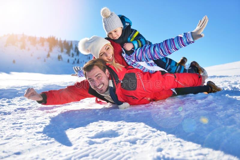 Lycklig ung familj som spelar i ny snö på härliga soliga den utomhus- vinterdagen i natur royaltyfria foton