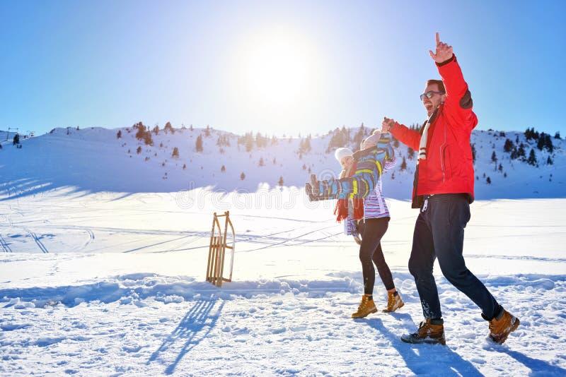 Lycklig ung familj som spelar i ny snö på härliga soliga den utomhus- vinterdagen i natur arkivfoto
