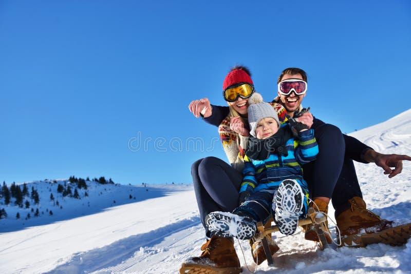 Lycklig ung familj som spelar i ny snö på härliga soliga den utomhus- vinterdagen i natur royaltyfria bilder