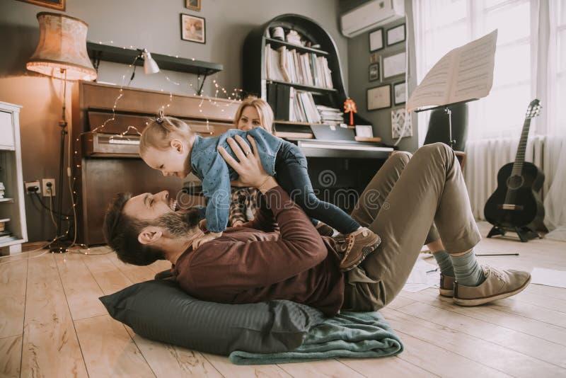 Lycklig ung familj som spelar på golvet royaltyfria foton