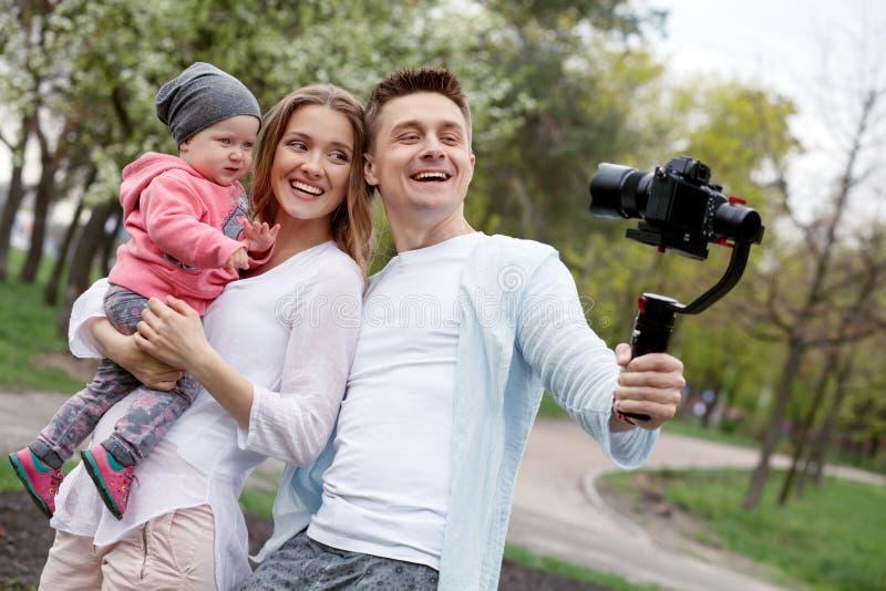 Lycklig ung familj som tar videopp selfies med hennes kamera på gimbalsteadycamen royaltyfria bilder