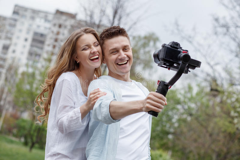 Lycklig ung familj som tar videopp selfies med hennes kamera på gimbalsteadycamen arkivbild