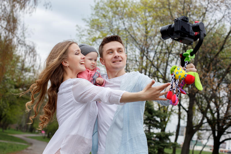 Lycklig ung familj som tar videopp selfies med hennes kamera på gimbalsteadycamen arkivfoton