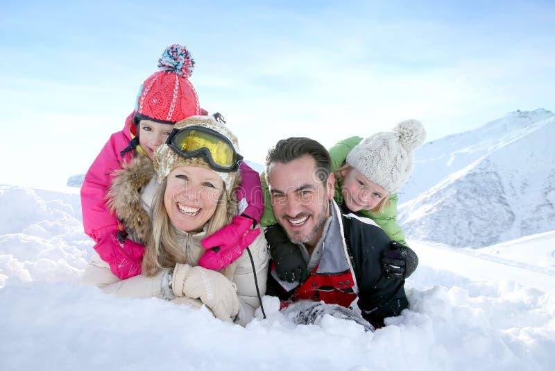 Lycklig ung familj som tycker om fri tid på vinterferier royaltyfri bild