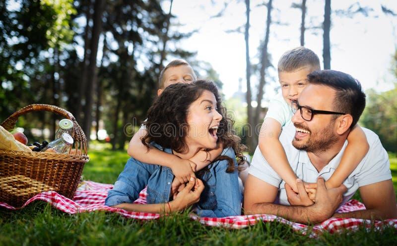 Lycklig ung familj som tycker om picknicken i natur arkivfoton