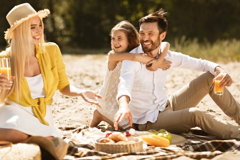 Lycklig ung familj som tycker om picknicken i natur arkivfoto