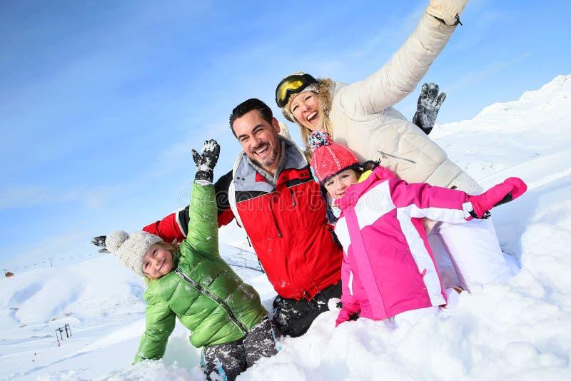 Lycklig ung familj som tycker om vinterferier arkivfoto