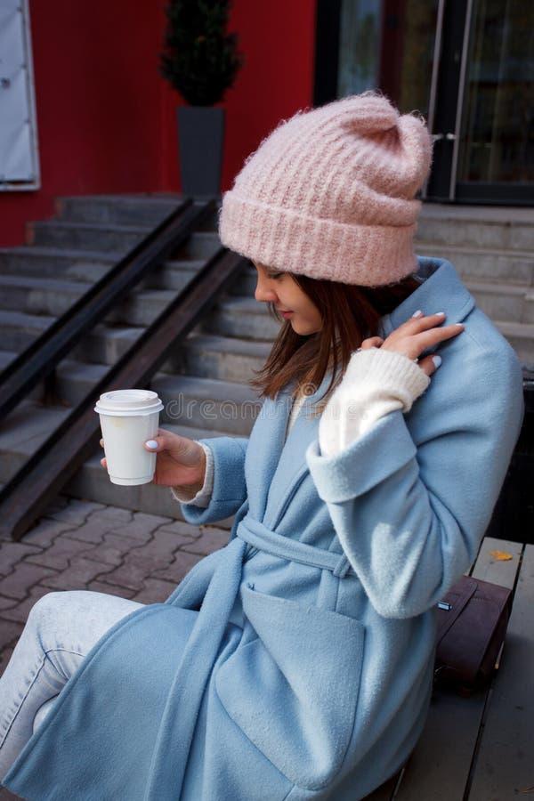 Lycklig ung flicka för stående som går på höststadsgatan som dricker kaffe för att gå arkivfoton