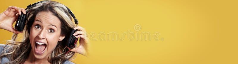 Lycklig ung flicka med hörlurar med mikrofon arkivbild