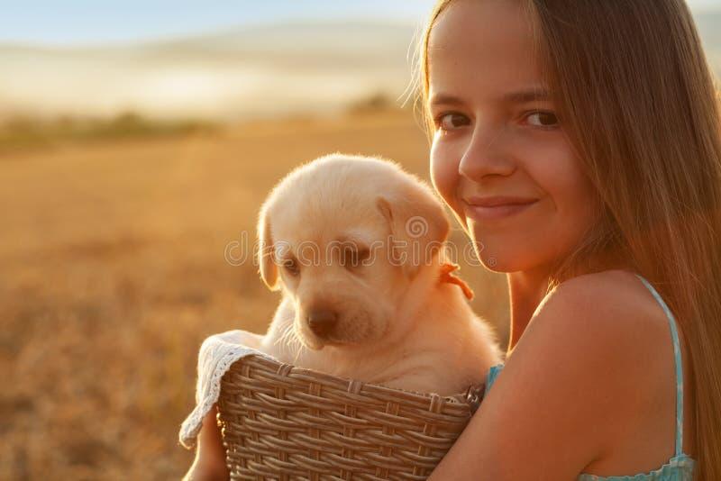 Lycklig ung flicka med hennes förtjusande labrador valphund fotografering för bildbyråer