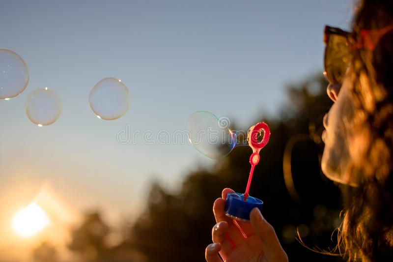 Lycklig ung flicka med s?pbubblor i h?st p? solnedg?ngen arkivbild