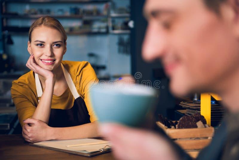 Lycklig ung flicka som håller ögonen på på klienten i kafé royaltyfri foto
