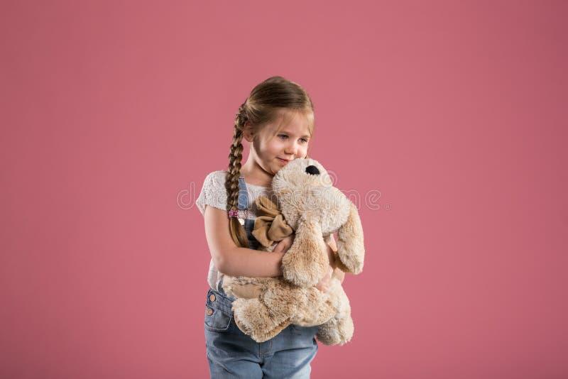 Lycklig ung flicka som kramar den välfyllda leksaken arkivbild