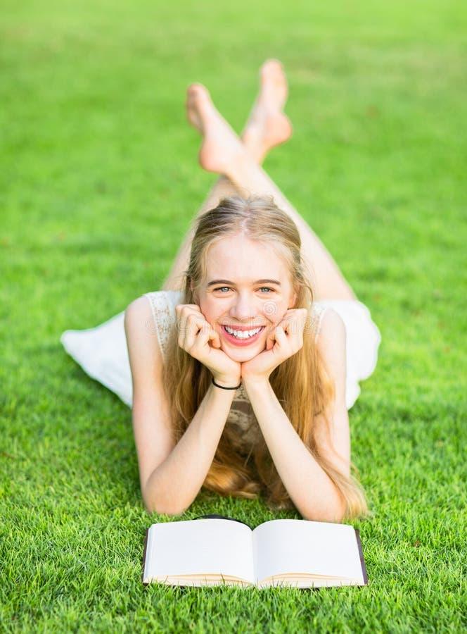 Lycklig ung flickaläsning på gräset arkivbild