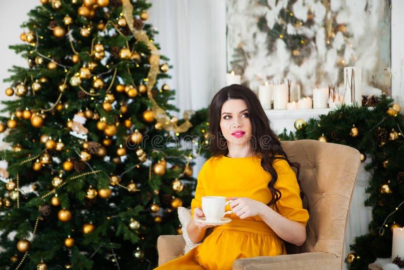 Lycklig ung gravid kvinna i gult klänningsammanträde nära Chrien arkivfoton
