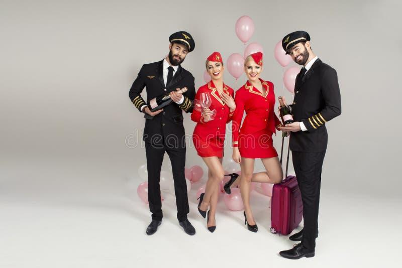 Lycklig ung grupp av piloter och stewardesser royaltyfria foton
