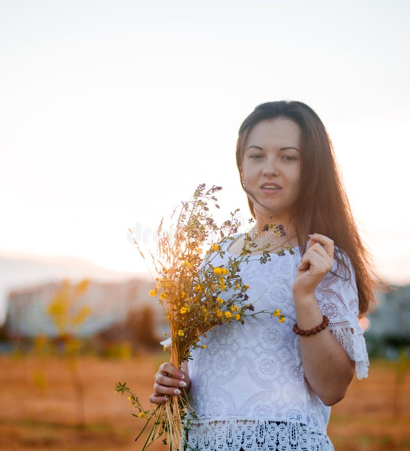 Lycklig ung härlig brunettflicka med H för lösa blommor för bukett royaltyfri fotografi