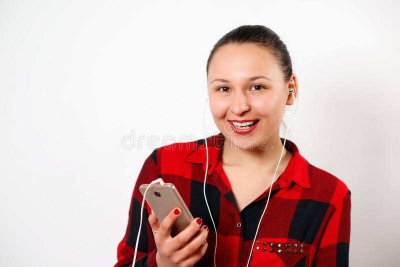 Lycklig ung härlig flicka i röd plädskjorta som lyssnar till musik, i hörlurar och att le P? vitbakgrund royaltyfri bild