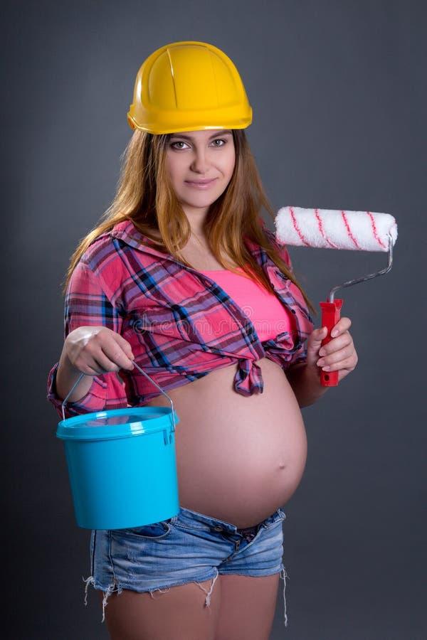 Lycklig ung härlig gravid kvinna i hjälm med byggmästaren till fotografering för bildbyråer