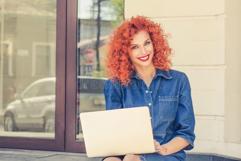 Lycklig ung härlig kvinna som använder bärbara datorn royaltyfri fotografi
