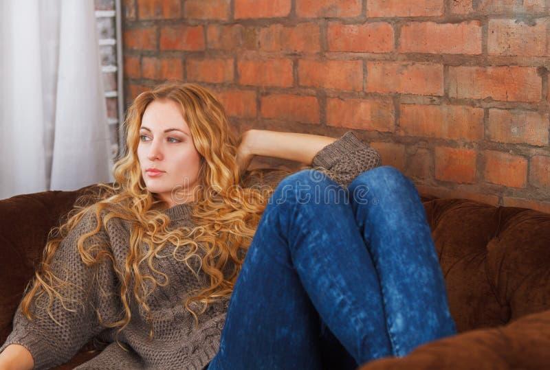 Lycklig ung härlig kvinna som hemma kopplar av på soffan arkivbild