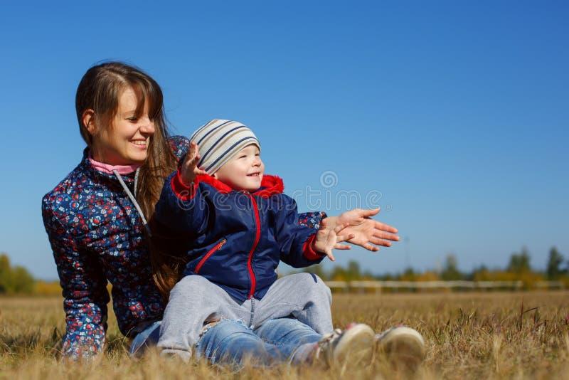 Lycklig ung härlig mather med behandla som ett barn på den utomhus- naturen royaltyfri fotografi