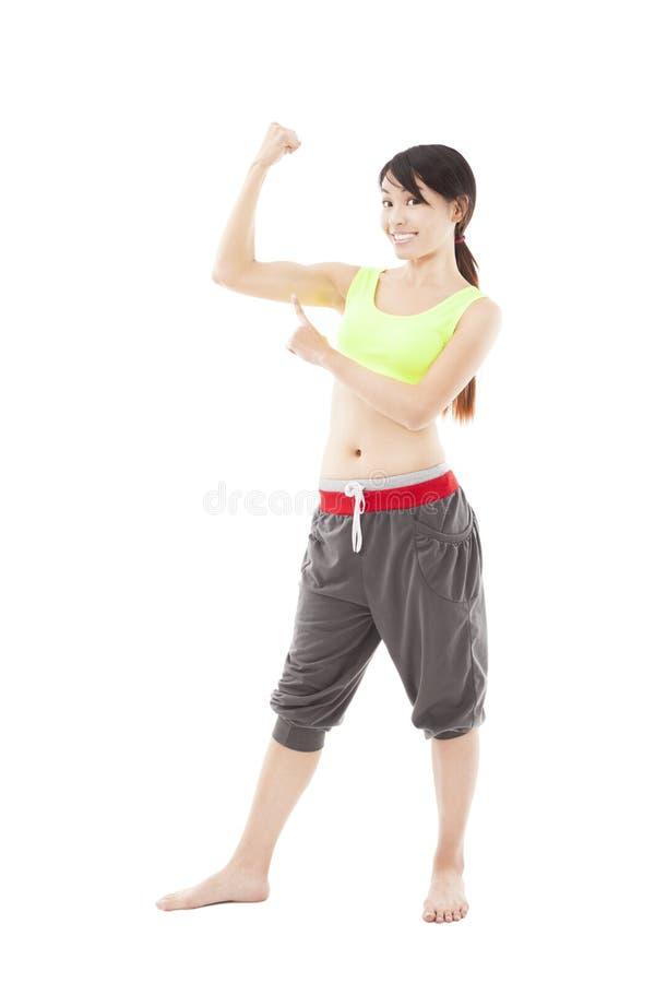 Ung konditionkvinna som pekar muskeln fotografering för bildbyråer