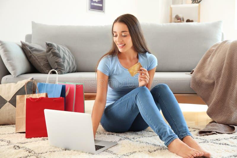 Lycklig ung kvinna efter online-shopping hemma arkivbild
