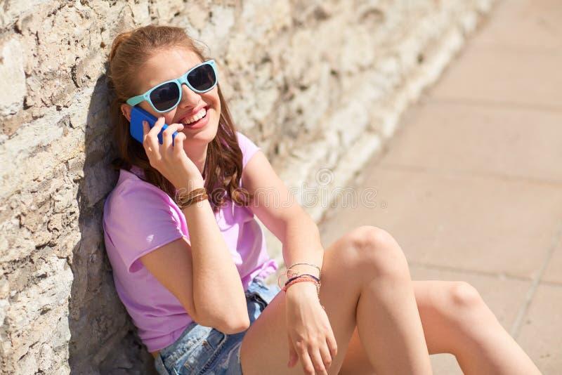 Lycklig ung kvinna eller flicka som kallar på smartphonen royaltyfri foto
