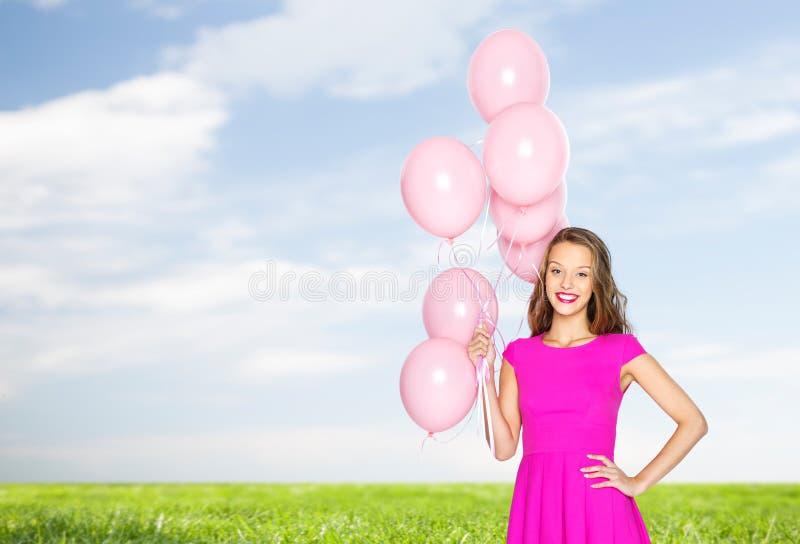 Lycklig ung kvinna eller tonårigt med heliumluftballonger royaltyfria bilder