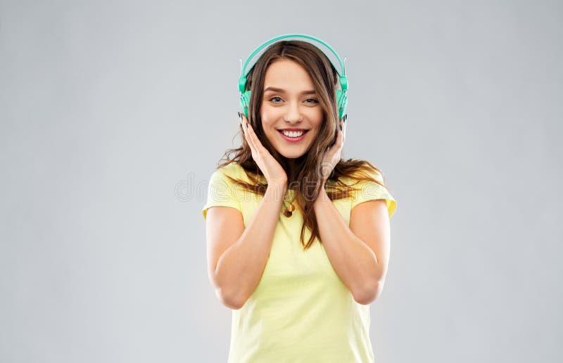 Lycklig ung kvinna eller ton?rs- flicka med h?rlurar royaltyfria foton