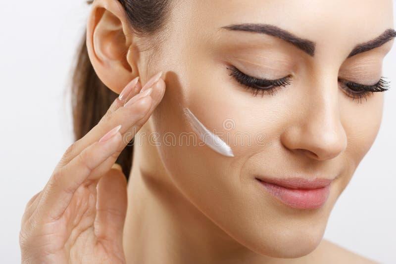 Lycklig ung kvinna för skönhet som applicerar kräm till hennes framsida Skincare och sk?nhetsmedelbegrepp Sk?nhetsmedel Omsorg f? fotografering för bildbyråer