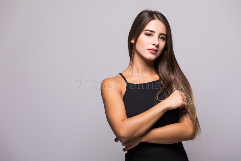 Lycklig ung kvinna för stående i svart klänning på grå bakgrund royaltyfri fotografi