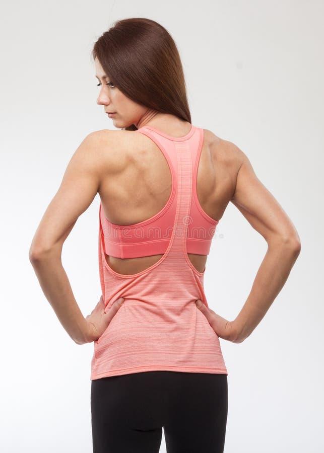 Lycklig ung kvinna, i att bekläda för sportar Muskulös konditionmodell på vit bakgrund tillbaka sikt royaltyfria foton