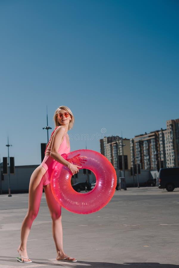 lycklig ung kvinna i baddräkt med den uppblåsbara cirkeln royaltyfria bilder