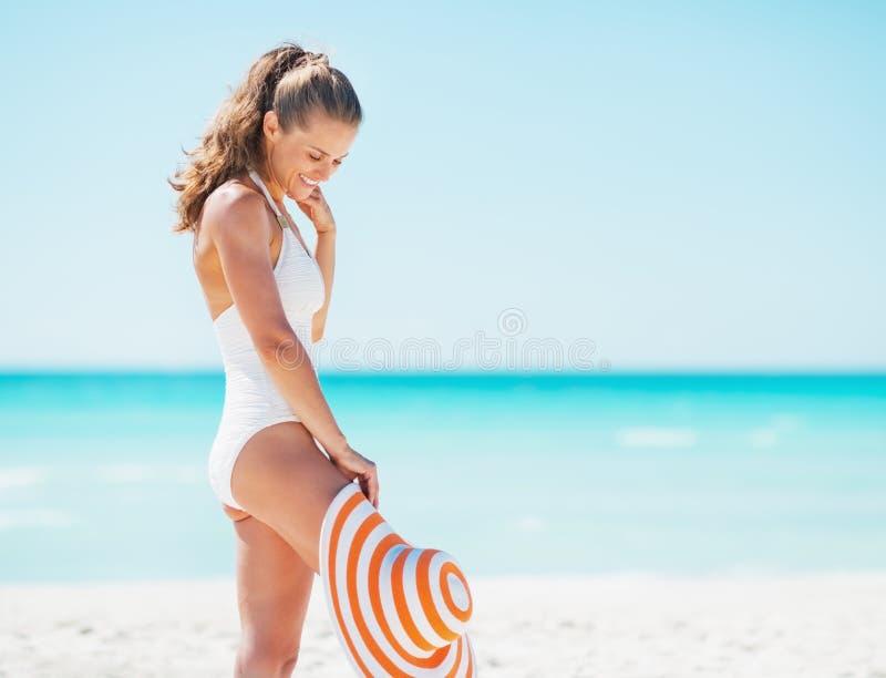 Lycklig ung kvinna i baddräkt med hatten som tycker om på stranden fotografering för bildbyråer