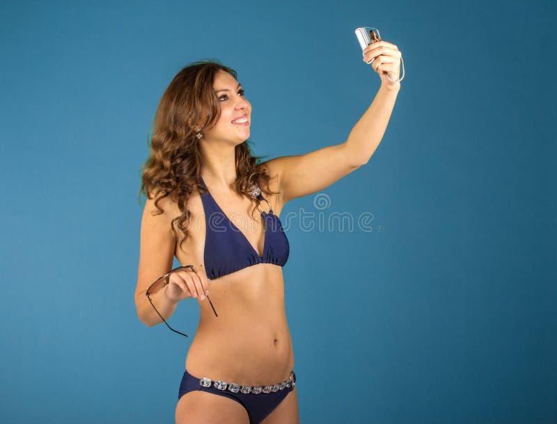 Lycklig ung kvinna i bikinibaddräkt och kamera på grön backgro royaltyfri fotografi