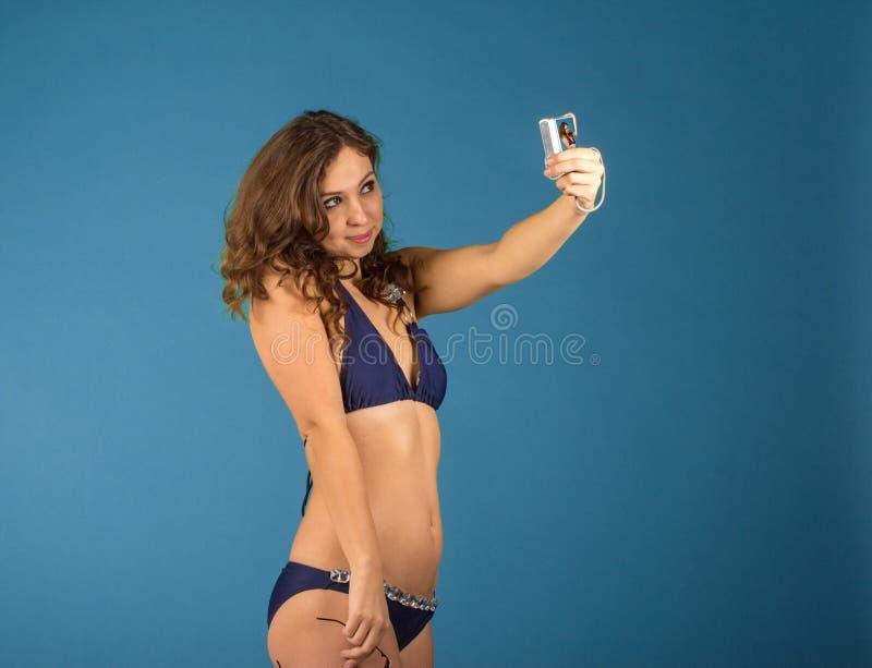 Lycklig ung kvinna i bikinibaddräkt och kamera på grön backgro arkivfoto
