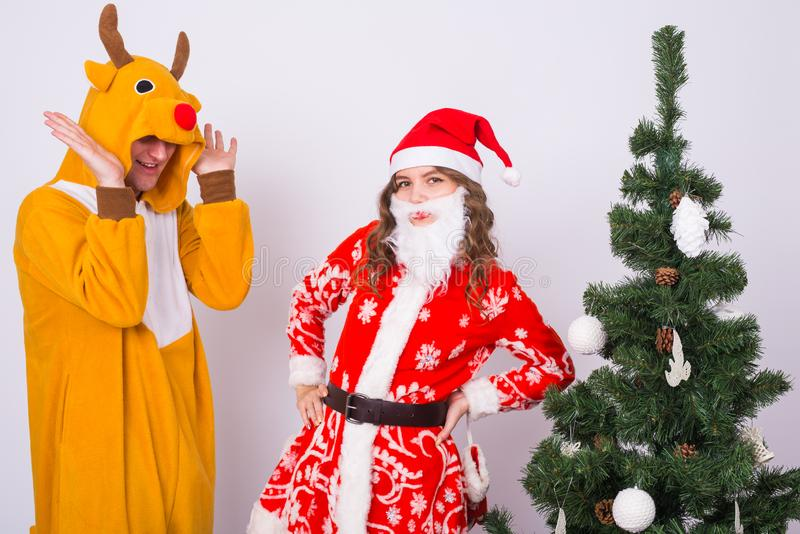Lycklig ung kvinna i den Santa Claus hatten och mannen i karnevaldräkt av hjortar Gyckel-, ferie-, skämt- och julbegrepp royaltyfri bild