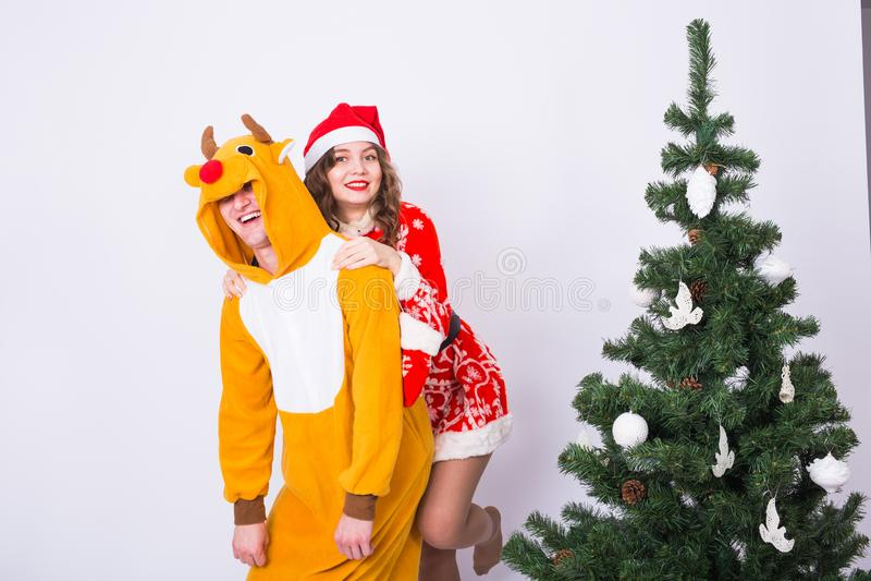 Lycklig ung kvinna i den Santa Claus hatten och mannen i karnevaldräkt av hjortar Gyckel-, ferie-, skämt- och julbegrepp arkivbild